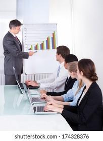 Mature Businessman Explaining Graph To His Colleagues