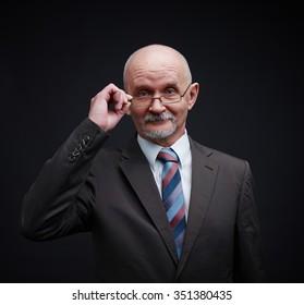 Mature businessman in eyeglasses looking at camera