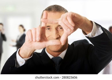 Mature businessman gesturing frame with hands.