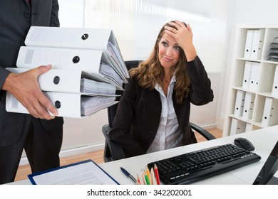 Mature Businessman Giving Pile Of Folders To Female Assistant In Office
