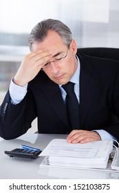 Mature Businessman Having Headache Sitting At Desk In Office