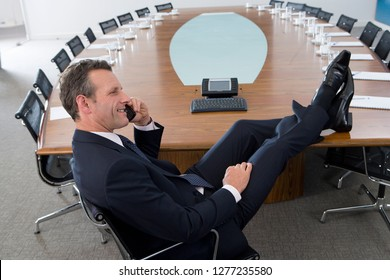 Mature businessman at head of boardroom conference table on phone