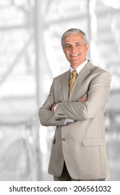 A mature businessman with his arms folded against blurred modern office interior. Vertical Format.