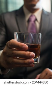 Mature businessman holding a glass of whisky in hotel.