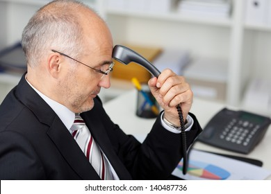 Mature businessman holding telephone receiver on his forehead