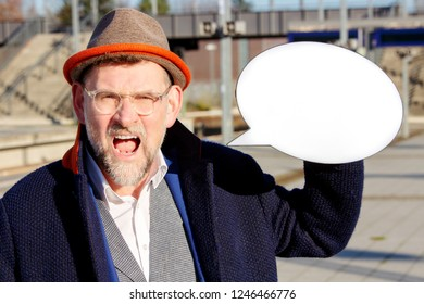 mature businessman looking angry and holding a speech bubble at train station