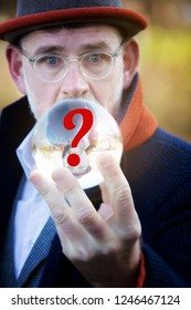 mature businessman looking at a glass sphere with red question mark