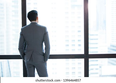 Mature businessman looking out of a window at the city skyline from an office building