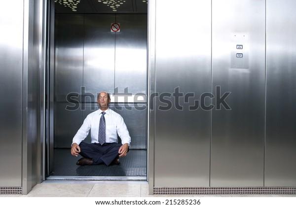 Mature businessman meditating in lift