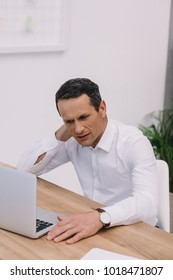 mature businessman with neck pain working with laptop at office