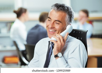 Mature businessman at the phone with colleagues in the background