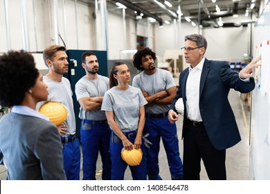 Mature businessman presenting business strategy on white board to group of industrial workers in a factory.