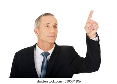 Mature businessman pressing abstract button.