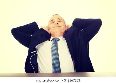 Mature businessman resting in armchair.