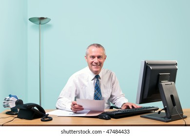 Mature businessman sat at an office desk working on some paperwork smiling to camera. The graphs and text on the documents were made and printed by me.