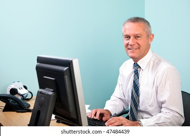 Mature businessman sat at an office desk working on his computer smiling to camera.