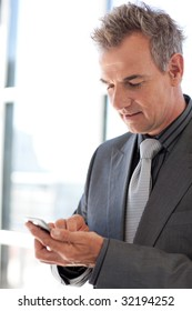 Mature businessman sending a text with a mobile phone