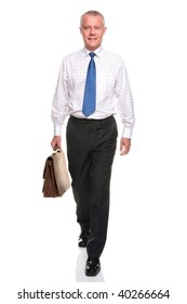 Mature businessman in shirt and tie walking towards carrying a briefcase, isolated on a white background.