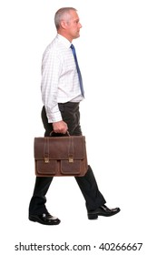 Mature businessman in shirt and tie walking towards carrying a briefcase, I've left shadow under the feet where grounded and there is a small amount of motion blur on his legs.