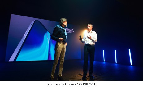 Mature businessman showing new cellphone and speaking with bearded engineer while standing against LED screen during presentation on stage