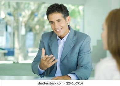 Mature businessman sitting at desk, smiling and gesticulating, young woman in blurred foreground
