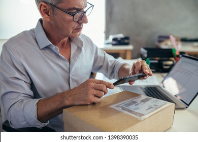 Mature businessman sitting at his desk and scanning a delivery box with his mobile phone. Man selling products online, scanning the barcode with his mobile phone.