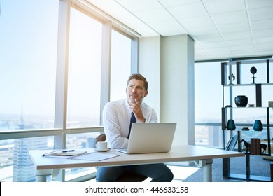 Mature businessman sitting at his desk in his office with large windows, his laptop open on front of him and looking away with a thoughtful and positive expression