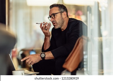 Mature businessman sitting in the hotel lobby with laptop making phone call. Male entrepreneur sitting in hotel waiting area making call.