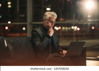 Mature businessman sitting in office lobby and making a video call. Businessman working late at night in office.