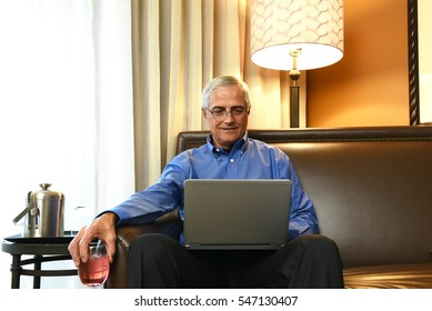 Mature Businessman sitting on the couch in his hotel room holding a drink while working on his laptop. Business travel concept.