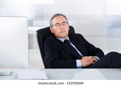 Mature Businessman Sleeping With Computer At Desk In Office