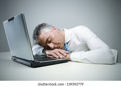 Mature businessman sleeping on his laptop