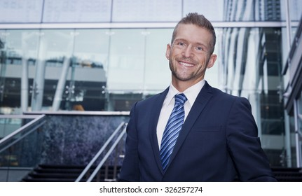 Mature Businessman Smiling At The Camera. He is outside of the office