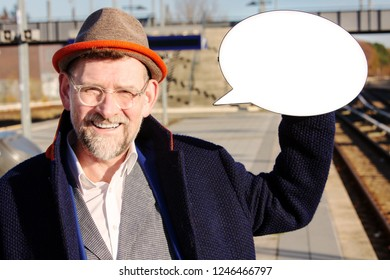 mature businessman smiling and holding a speech bubble at train station