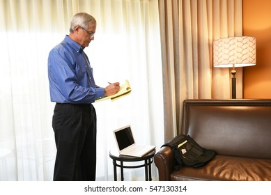 Mature Businessman standing in his hotel room making notes on a legal pad. Business travel concept.