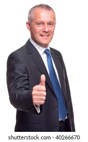 Mature businessman in suit and tie giving a thumbs up gesture towards camera, isolated on a white background.