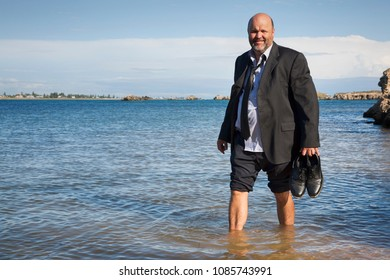 A mature businessman taking time out and wading at the beach.
