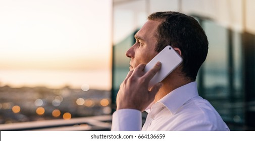 Mature businessman talking on a cellphone while standing on an office building balcony overlooking the city at sunset