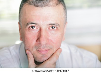 Mature businessman thinking about something and looking straight at camera