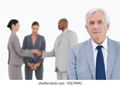 Mature businessman with trading partners behind him against a white background