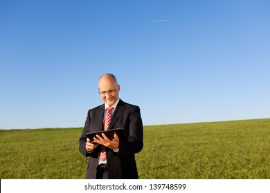 Mature businessman using digital tablet while standing against clear sky
