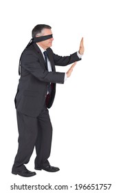 Mature businessman walking with blindfold on white background
