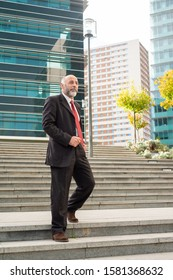 Mature businessman walking down stairs. Low angle view of confident bearded businessman in formal wear walking on stairs and looking aside on urban city street. Business concept