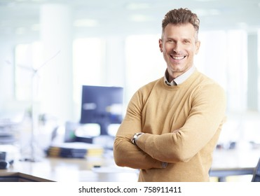 A mature businessman wearing casual clothes while standing arms crossed in the office.