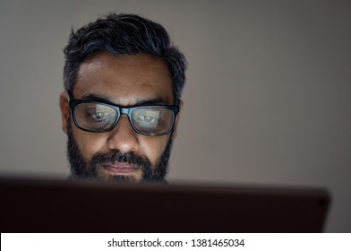 Mature businessman wearing eyeglasses while using laptop in a dark office. Middle eastern man working late at office. Overworked man with specs in front of laptop with copy space.
