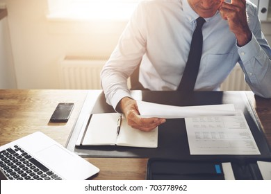 Mature businessman wearing a shirt and tie sitting alone at his desk in an office reading through paperwork