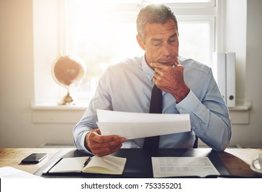 Mature businessman wearing a shirt and tie reviewing documents while sitting alone at his desk in an office