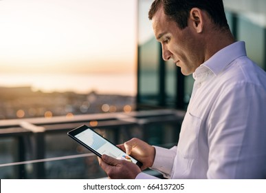Mature businessman working with a digital tablet while standing outside on an office building balcony overlooking the city at dusk