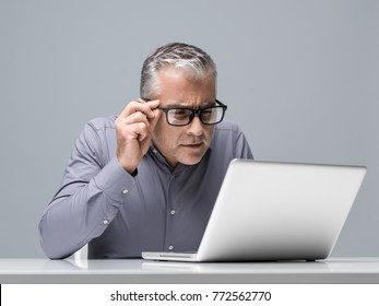 Mature businessman working with a laptop and having vision problems, he is staring closely at the computer screen and adjusting his glasses