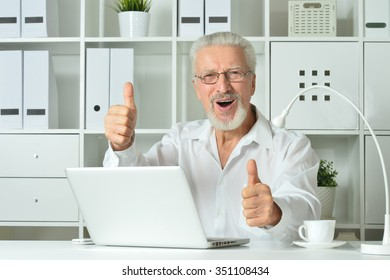 Mature businessman working with laptop in office with thumbs up